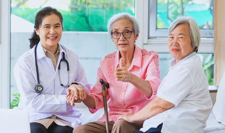 nurse and two seniors are smiling