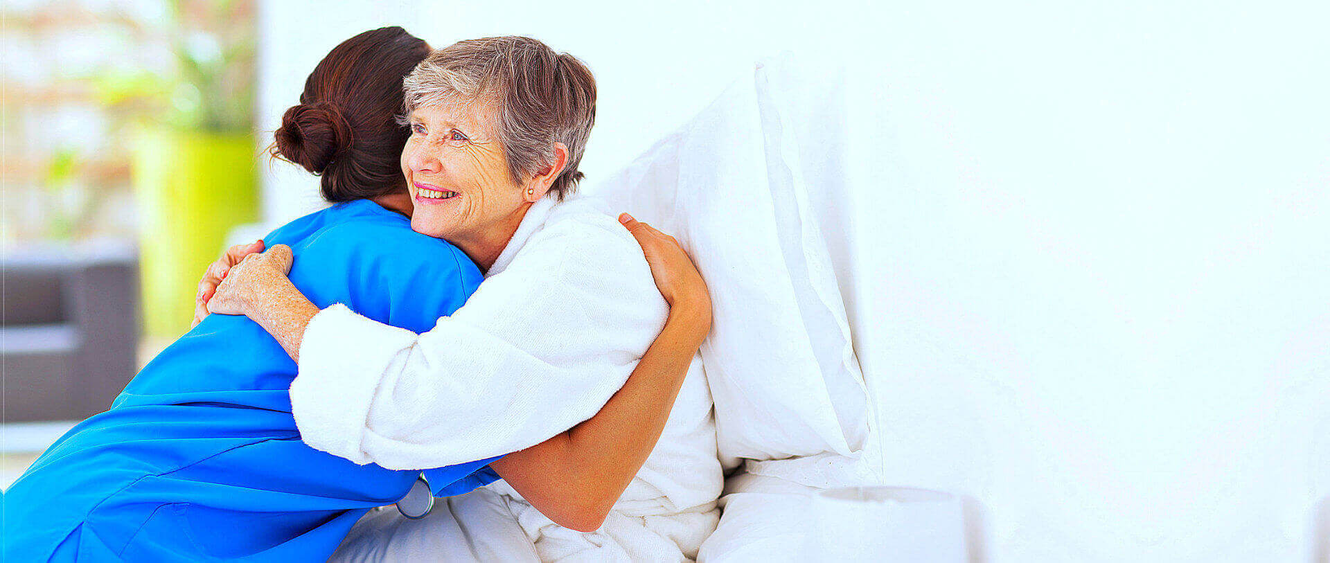 nurse and senior woman are hugging together while smiling