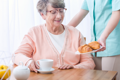 caregiver serving breakfast to a senior woman
