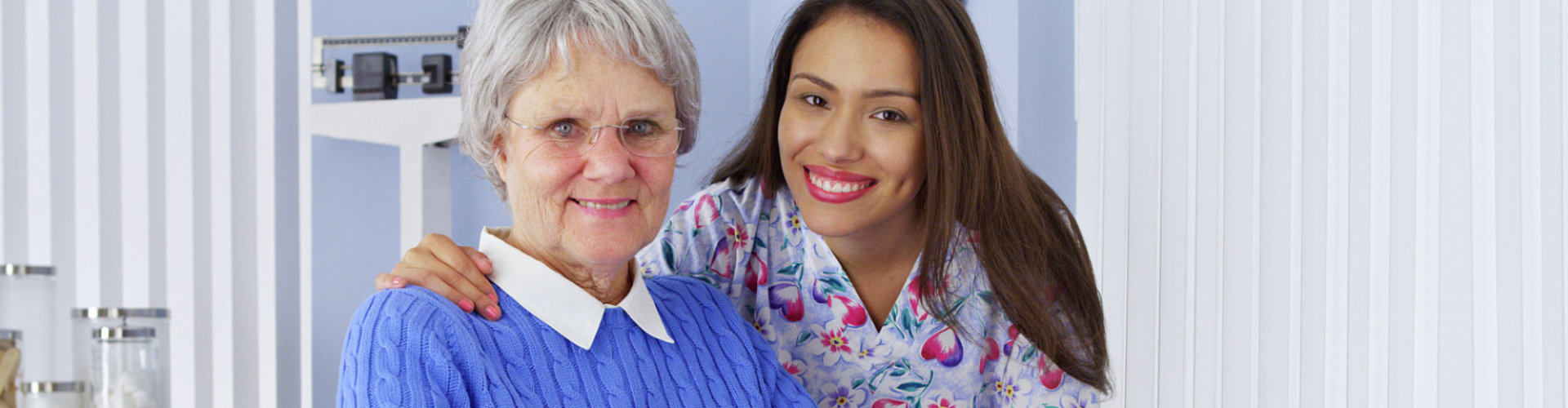 caregiver and senior woman are smiling at the hospital
